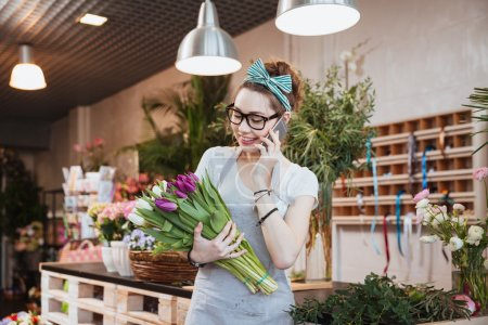 Cheerful woman florist holding tulips and talking on mobile phone