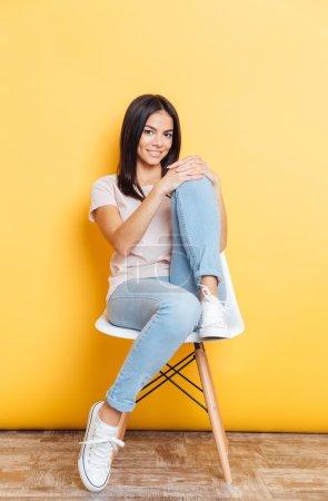Heureuse femme séduisante, assis sur la chaise