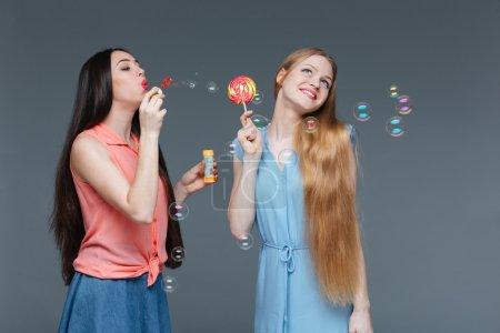 Photo pour Deux joyeux belles jeunes femmes mangeant sucette colorée et soufflant des bulles sur fond gris - image libre de droit