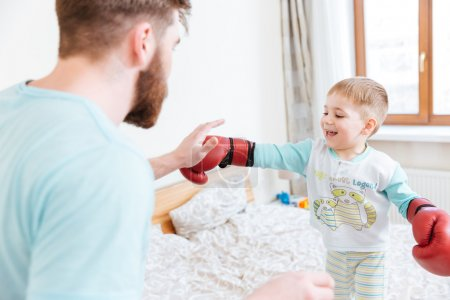 Photo pour Barbu jeune père jouer avec son petit fils dans des gants de boxe à la maison - image libre de droit