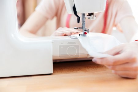 Woman seamstress sews clothes and put thread in needle