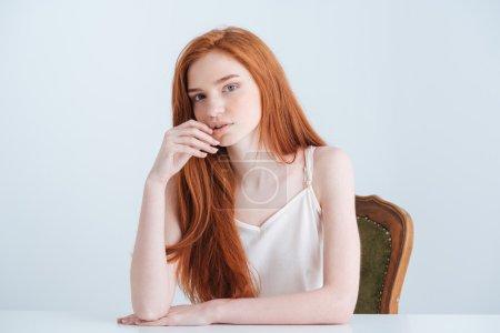 Photo pour Femme belle rouquine assis à la table et regarder la caméra isolé sur fond blanc - image libre de droit