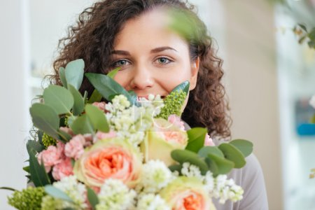 Happy woman holding bouquet of flowers and smiling