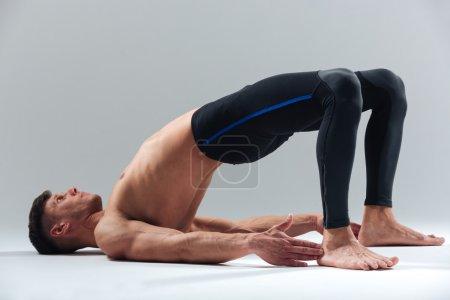 Photo pour Fitness homme faisant pose de yoga isolé sur un fond blanc - image libre de droit