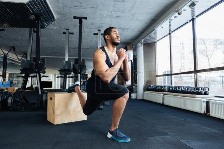 Photo for Muscular fitness man doing squats using wooden stand in the gym - Royalty Free Image