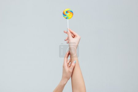 Female arms holding lollipop on stick
