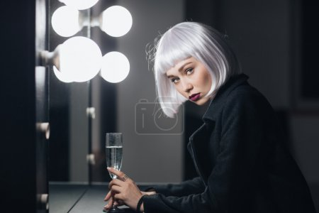 Beautiful woman drinking champaigne in dressing room