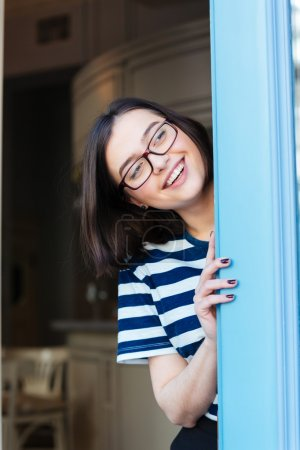 Cheerful woman in glasses looking out of cafe and smiling