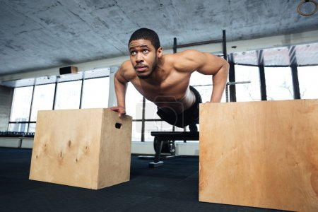 Healthy fitness man doing push-ups in the gym
