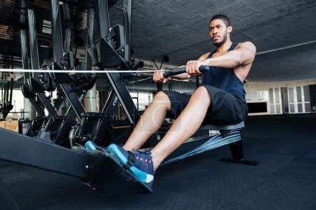 Fitness man using rowing machine at gym