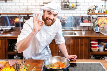 Photo for Smiling handsome chef cook preparing food and showing ok gesture on the kitchen - Royalty Free Image