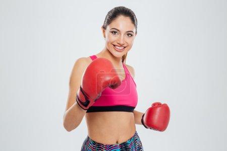 Photo pour Femme heureuse en regardant la caméra isolé sur fond blanc des gants de boxe - image libre de droit