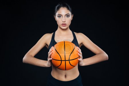 Pretty fitness woman holding and posing with basketball ball