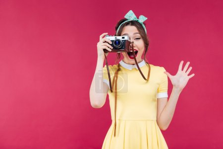 Happy pretty pinup girl taking pictures with vintage camera