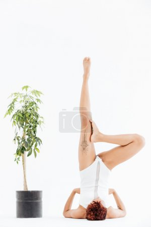 Concentrated african young woman doing balancing yoga pose