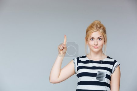 Cute lovely young woman standing and pointing up