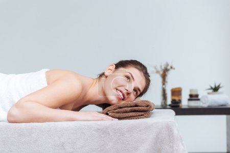 Happy pretty young woman smiling and lying in spa salon