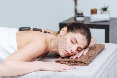 Woman relaxing and receiving hot stone massage in spa salon