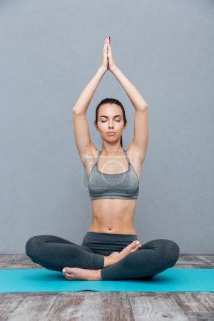 Young woman doing yoga exercise Padmasana (Lotus Pose)