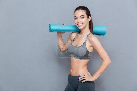 Photo for Attractive smiling sportswoman holding yoga mat isolated over grey background - Royalty Free Image