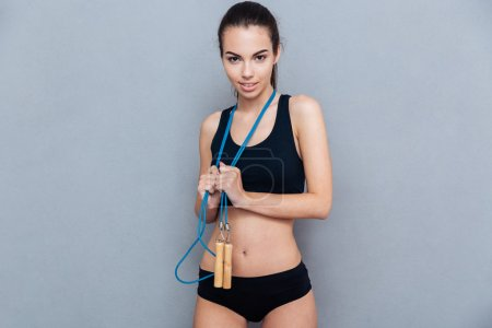 Attractive sport girl holding jumping rope and looking at camera