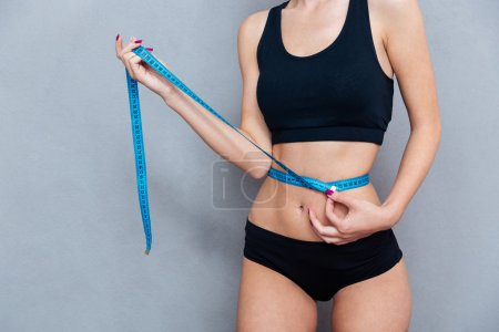 Woman measuring her waist with centimeter tape on grey background