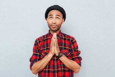 Photo pour Beau jeune homme afro-américain au chapeau noir debout et priant - image libre de droit