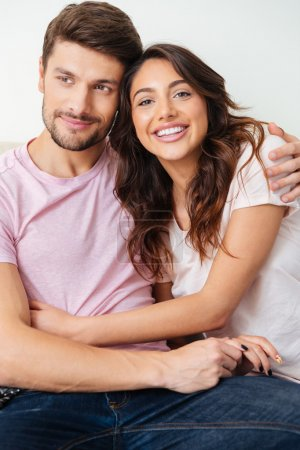 Photo for Close-up portrait of a beautiful smiling couple sitting on the couch over white background - Royalty Free Image
