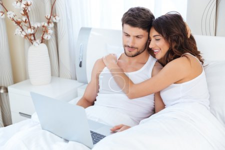 Couple hugging and using a computer lying on their bed