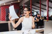 Smiling inspired young woman making business plan in office