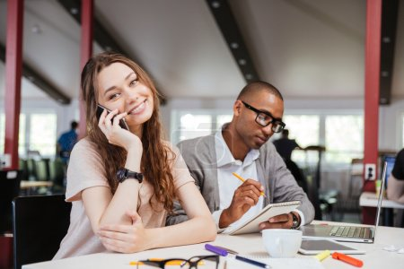 Cheerful business woman working with serious african man in office