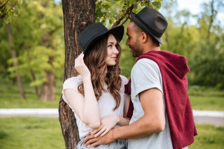 Happy young couple standing and embracing in park