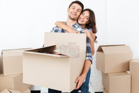 Smiling young couple carrying cardboard boxes and hugging