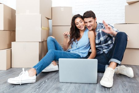 Happy couple sitting on floor moving in a new house