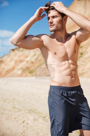 Attractive shirtless young man standing on beach