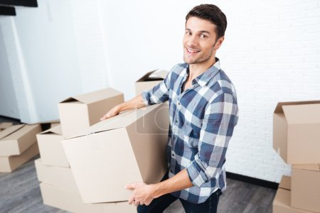 Photo for Happy man moving in and carrying carton boxes in a new flat - Royalty Free Image
