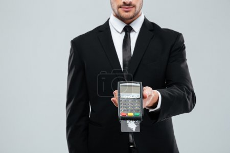 Businessman in black suit holding bank terminal with credit card