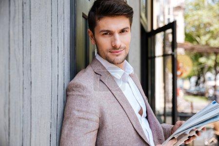 Photo pour Gros plan portrait d'un beau homme debout avec journal au café en plein air - image libre de droit