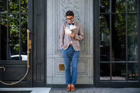 Photo pour Jeune homme intello élégant lisant des livres à l'extérieur - image libre de droit