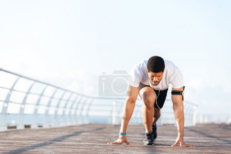 Photo for Concentrated african young sportsman is ready to start running outdoors - Royalty Free Image