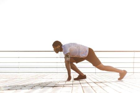 Sportsman preparing for start running in the morning at sunrise
