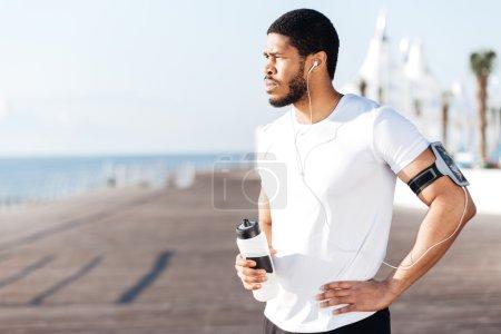 Photo pour Beau jeune sportif africain debout et boire de l'eau à l'extérieur - image libre de droit