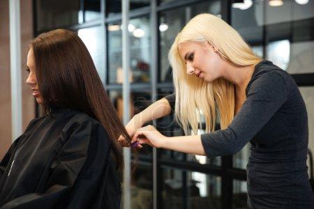 Photo pour Jeune coiffeuse faisant une coupe de cheveux à un client dans un salon de beauté - image libre de droit