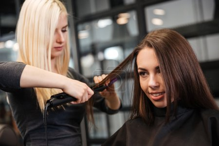 Hairstylist curling hair woman client in hairdressing beauty salon