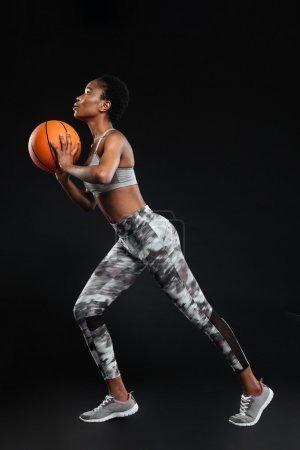 Full length portrait of a sports woman holding basketball ball