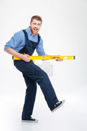 Cheerful male builder playing with waterpas