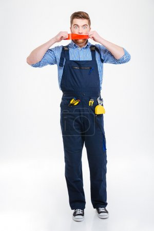 Shocked worker in overall with mouth covered by adhesive tape