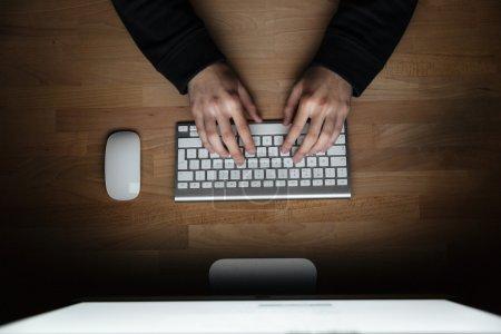 Photo pour Vue du dessus des mains du jeune homme tapant sur le clavier - image libre de droit