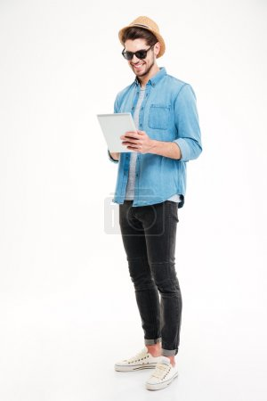 Photo for Full length of happy handsome young man using tablet over white background - Royalty Free Image