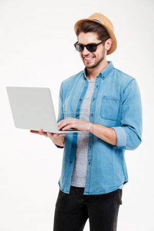 Photo for Smiling attractive young man in sunglasses and hat standing and using laptop - Royalty Free Image